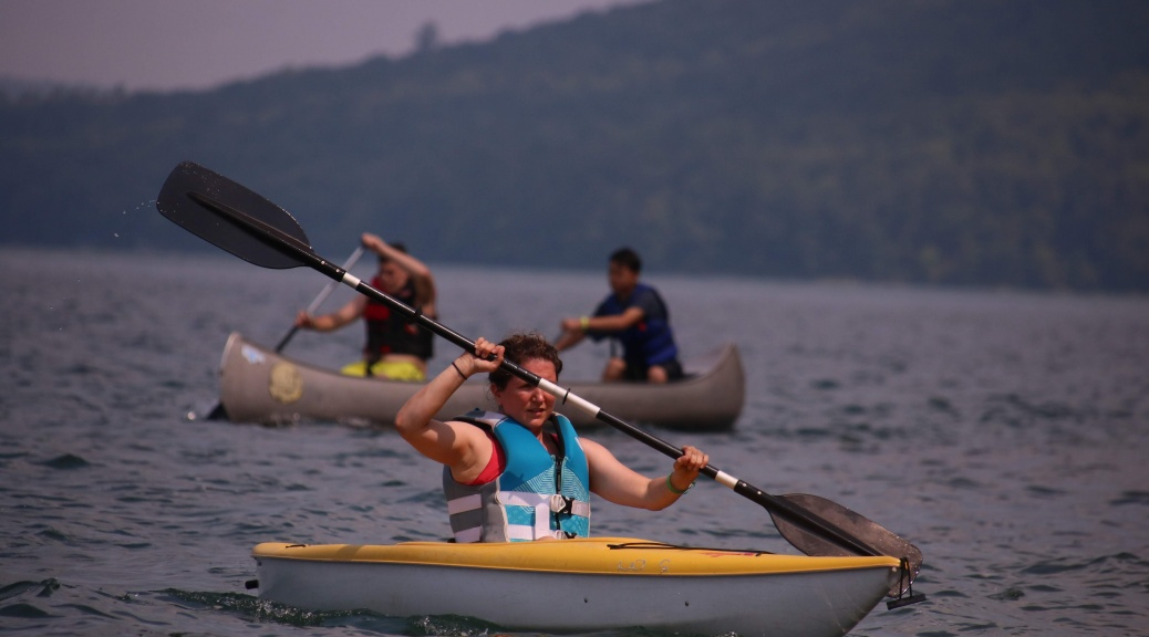 girl rows in a kayak boat on the lake