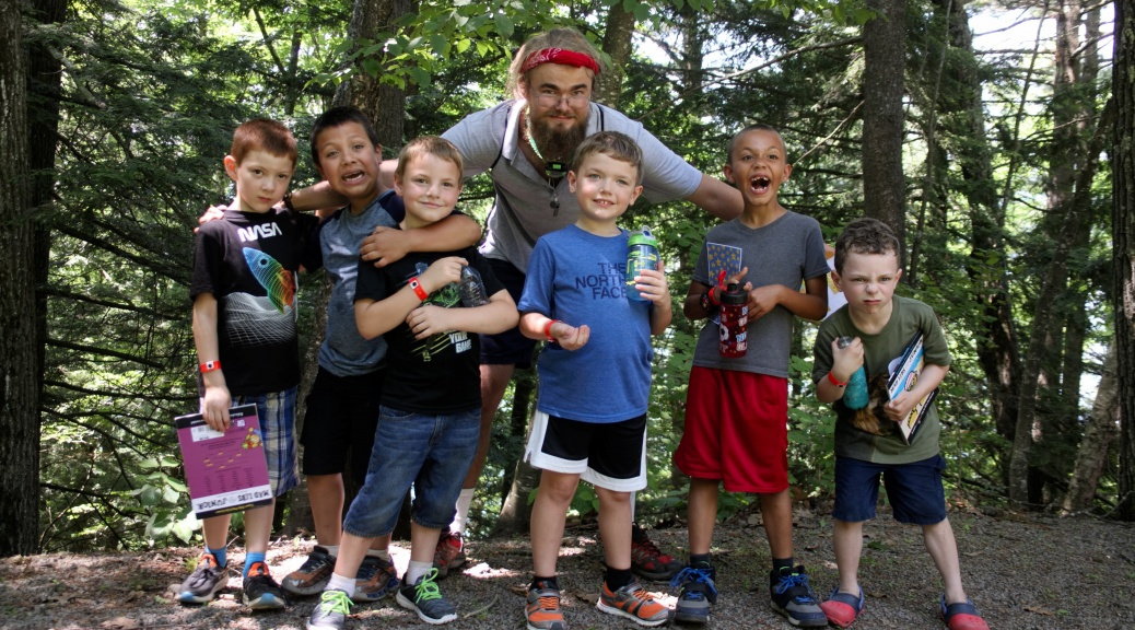 six kids and their counselor pose for a photo in the woods
