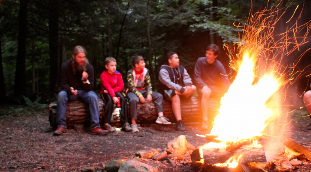 young campers and leaders sit around a campfire